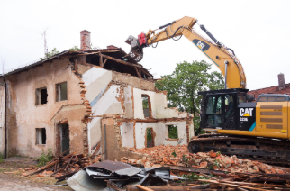 Photo of an excavator demolishing an old building