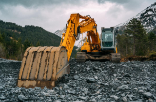 Large excavator scooping gravel in the mountains