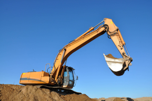 Excavtor scooping dirt with blue sky in the background