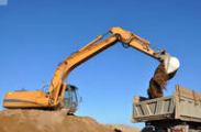 Photo of excavator dumping dirt into the back of a dump truck